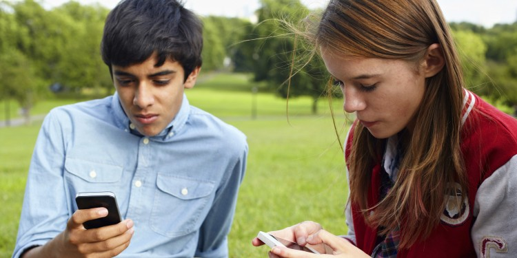 Teenage boy and girl using smartphones